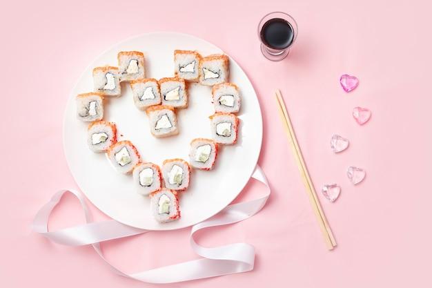 ピンクのテーブルに箸と醤油を添えて、ハートの形に寿司を並べます。 Premium写真