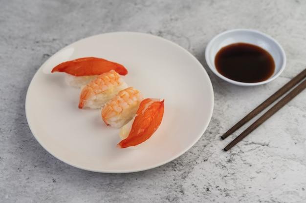 Sushi è in un piatto con le bacchette e salsa di immersione su un pavimento di cemento bianco. Foto Gratuite