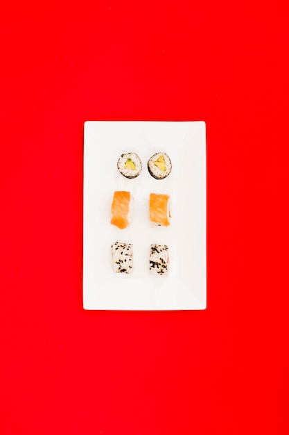 Sushi maki with salmon and philadelphia roll on white tray over bright red surface Free Photo