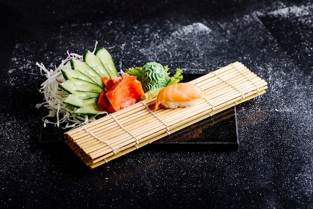 Sushi mat, salmon roll, wasabi, red marinated ginger and cucumber slices. Free Photo