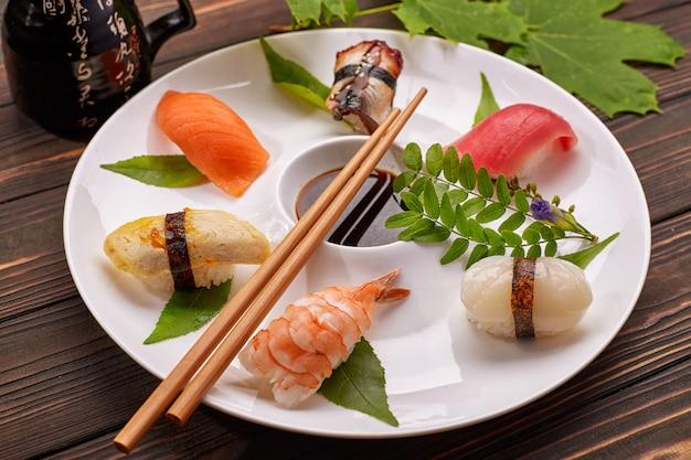 Суши нигири с тунцом, лососем, креветками, морским гребешком, угрем, омлетом, на белой тарелке с соевым соусом Premium Фотографии