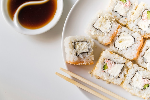 Sushi plate with sauce and chopsticks Free Photo
