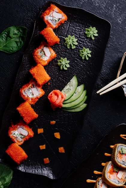 Sushi red rolls with wasabi, ginger and cucumber in black plate. Free Photo