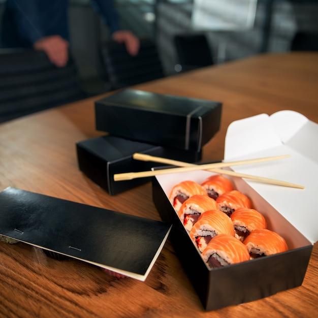 젓가락으로 작업 영역에 스시 롤 배달 상자. 사무실 점심 프리미엄 사진