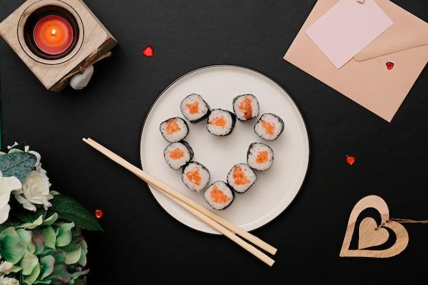 Суши ролл в форме сердца, на тарелку. квартира лежала. Premium Фотографии