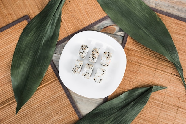 Sushi roll on white plate with green leaves and placemat Free Photo