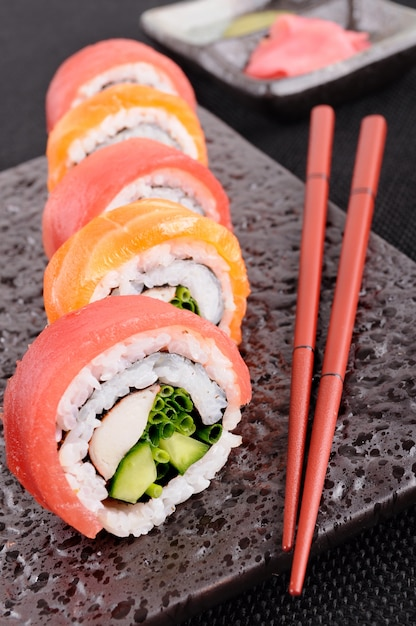 Sushi roll with chopsticks closeup Free Photo