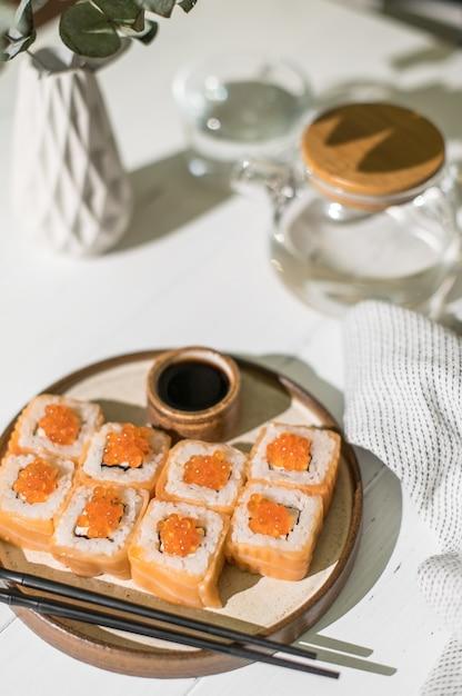 サーモンとキャビアの巻き寿司。日本食。白い木製の背景にサーモンとキャビアのロールパン Premium写真