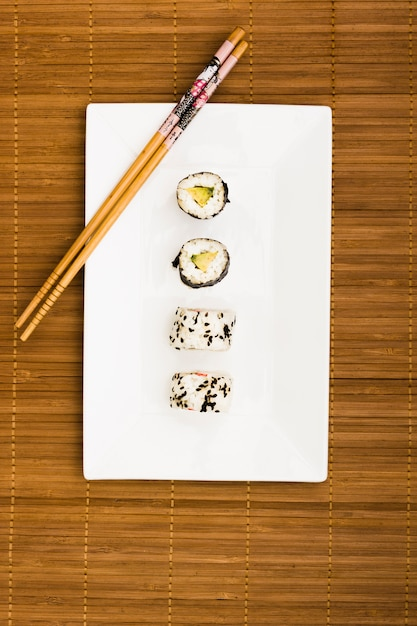 Sushi rolls arranged in a row on white place with wooden chopsticks over placemat Free Photo