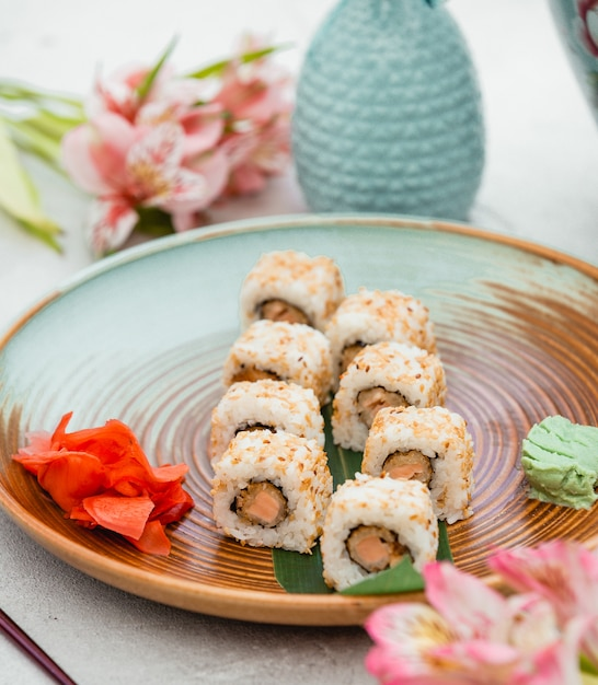 Sushi rolls in brown green plate with ginger and wasabi. Free Photo
