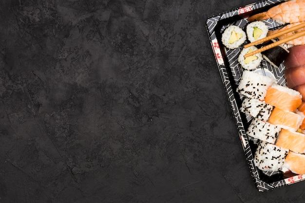 Sushi rolls and sashimi arranged on tray over textured floor Free Photo