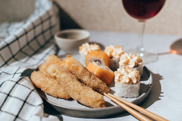 サーモン、チーズクリーム、エビフライをグレーのプレートと赤ワインのグラスにセットした巻き寿司 Premium写真