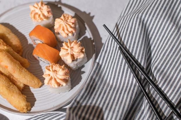 鮭、チーズクリーム、エビフライをグレーのプレートにセットした巻き寿司 Premium写真