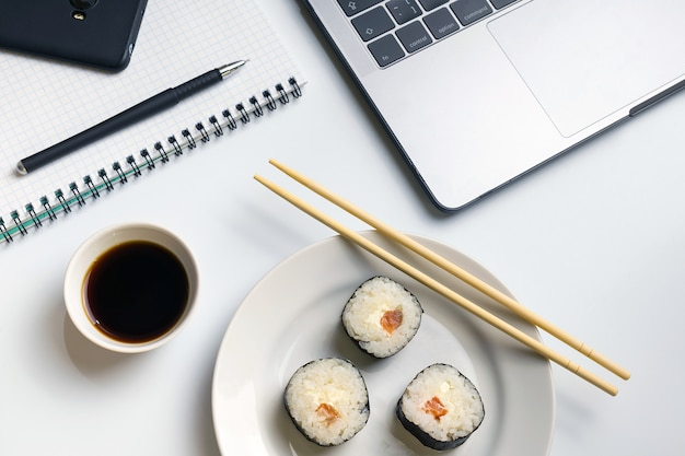 Sushi rolls snacking at work. break time for sushi eating with soy sauce. Premium Photo
