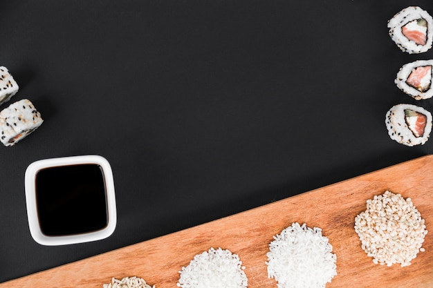 Sushi rolls; soya sauce and uncooked rice on wooden tray over the black background Free Photo