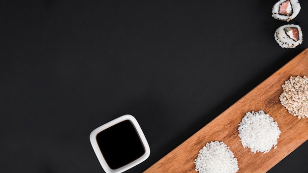 Sushi rolls; soya sauce with white and brown uncooked rice on black background Free Photo