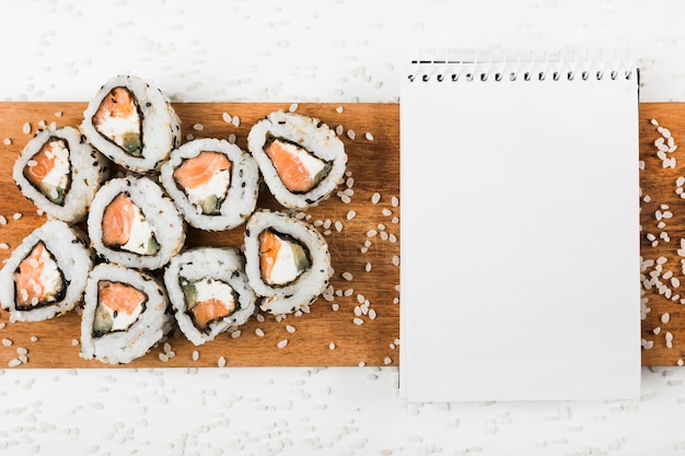 Sushi rolls and spiral notepad on wooden tray with splatter of uncooked rice Free Photo