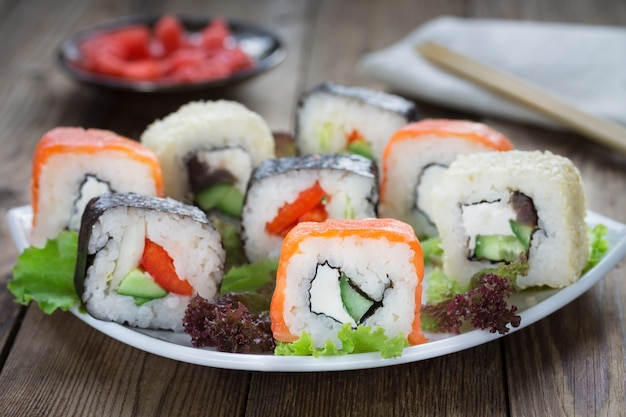 Sushi rolls on a white plate with ginger and a kitchen napkin . Premium Photo