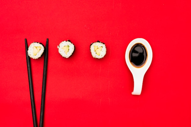 Sushi rolls with chopsticks and soya sauce over red background Free Photo