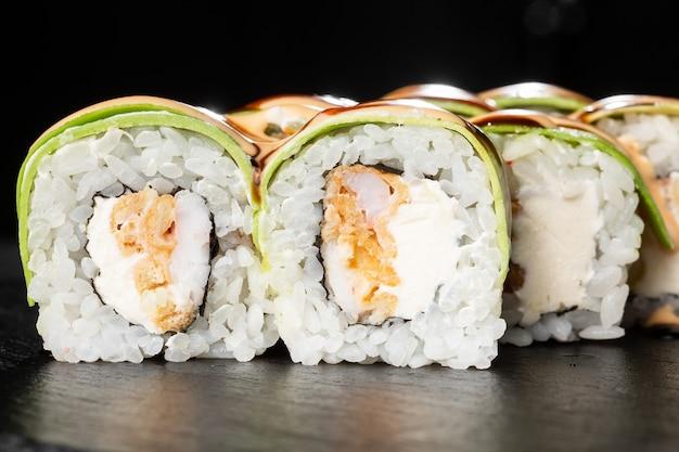 天ぷら海老のグリル、アボカド、オムレツ、クリームチーズが入った巻き寿司。 Premium写真