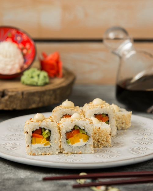 Sushi rolls with red and yellow bell pepper, cucumber topped with sesame Free Photo