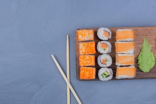 Rotoli di sushi con salsa wasabi su un piatto di legno Foto Gratuite