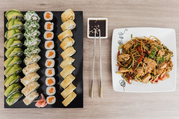 Sushi rolls with yakisoba and soy sauce on a wooden table Premium Photo