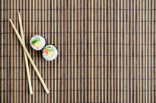 Sushi Rolls And Wooden Chopsticks Lie On A Bamboo Straw