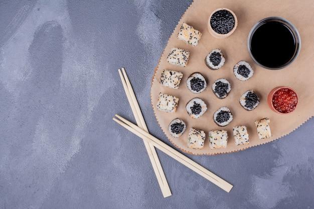 寿司セット。巻き寿司とアラスカ巻き寿司は、箸、キャビア、醤油で木の板に巻かれます。 無料写真