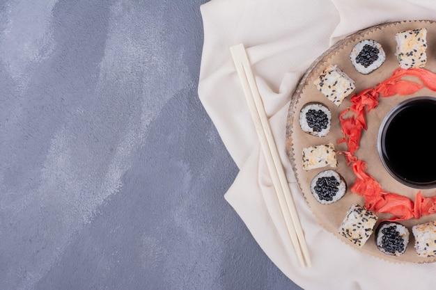 寿司セット。巻き寿司とアラスカの寿司は、テーブルクロス、生姜のピクルス、醤油を添えて木の板に巻かれています。 無料写真