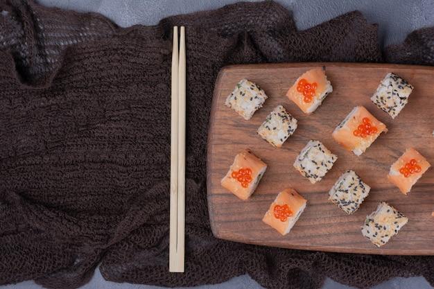 寿司セット。フィラデルフィアとアラスカは箸で木の板に転がります。 無料写真