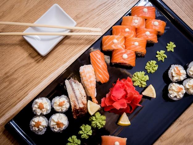 寿司セット。木の板にサーモン、ウナギ、キャビアを巻き。レストラン。 Premium写真