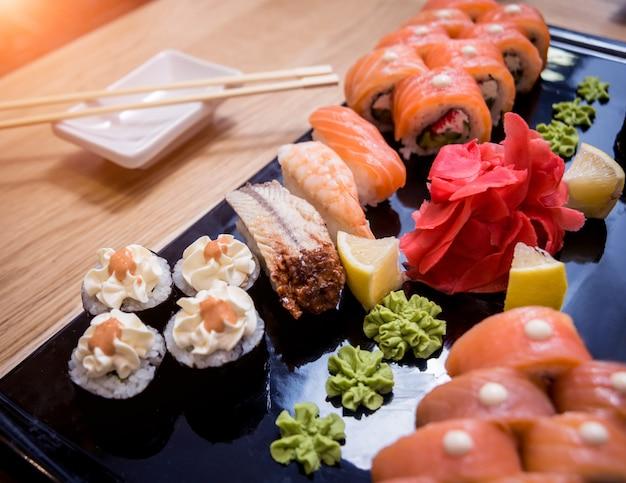 寿司セット。木の板にサーモン、ウナギ、赤キャビアを巻き。飲食店。 Premium写真