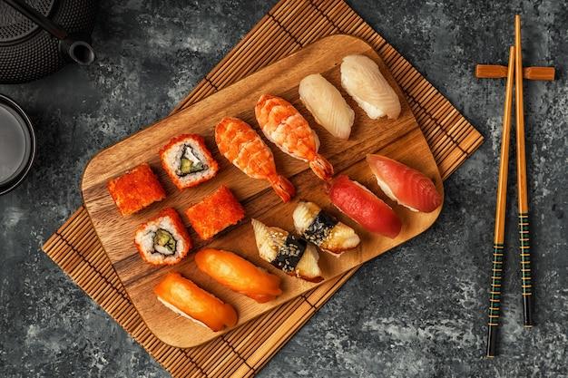 寿司セット:木の板に寿司と巻き寿司、上面図。 Premium写真