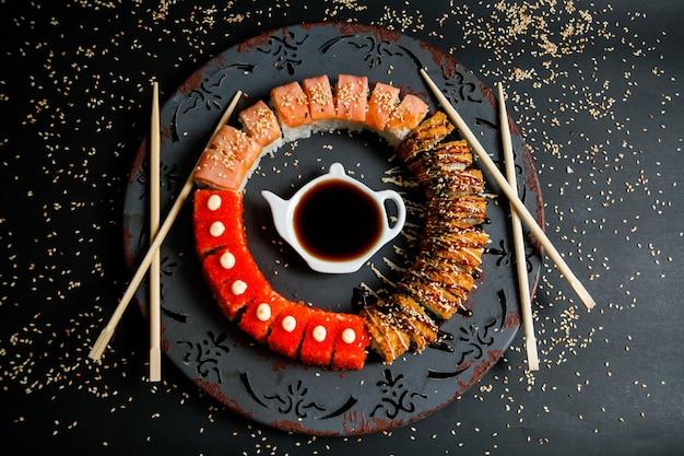 Суши-сет с авокадо, лососем, крабом, семенами кунжута и соевым соусом Бесплатные Фотографии
