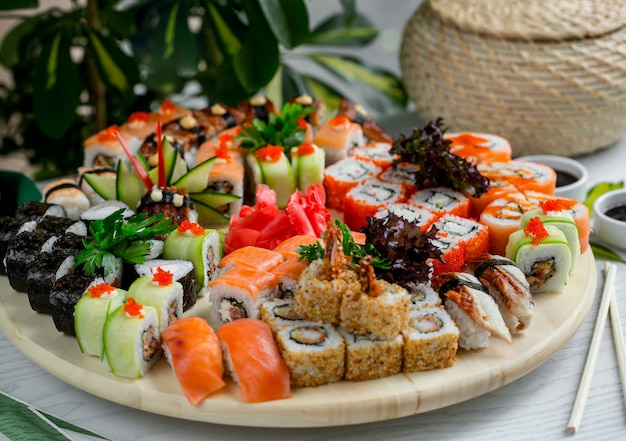 Sushi set with hot and cold rolls on wood platter Free Photo
