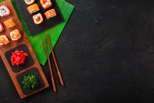 Sushi set with wasabi and ginger on black stone tray on black table. top view Premium Photo