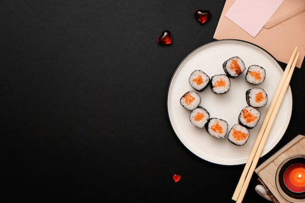 Sushi for valentines day - roll in heart shape, on plate on black background. flat lay. space for text. Premium Photo