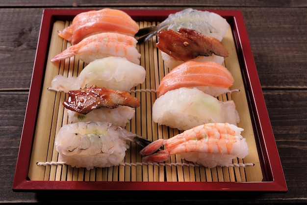 Sushi various assortment red bamboo tray Free Photo