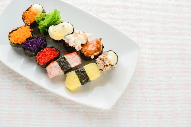 Sushi on white plate, tuna, salmon, sea bass, sweet egg, shrimp sushi, japanese food Premium Photo