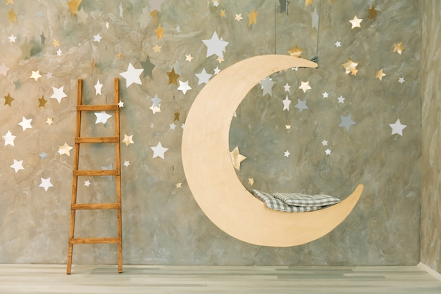 Suspended swing in the shape of the moon with stars. Premium Photo