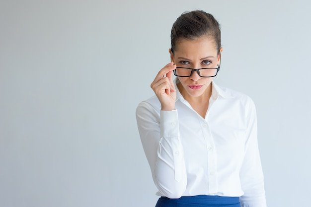 Suspicious arrogant young businesswoman looking over her glasses. Free Photo