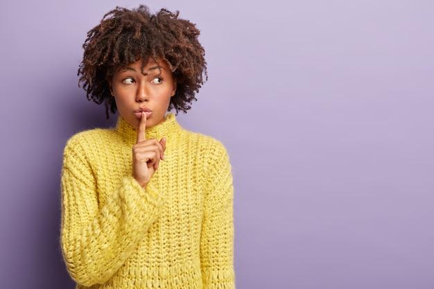 Подозрительная красивая женщина просит быть с пальцем на губах, смотрит в сторону, сообщает секретную информацию, сосредоточена в стороне, просит держать рот закрытым, носит желтую одежду, изолирована на фиолетовой стене Бесплатные Фотографии