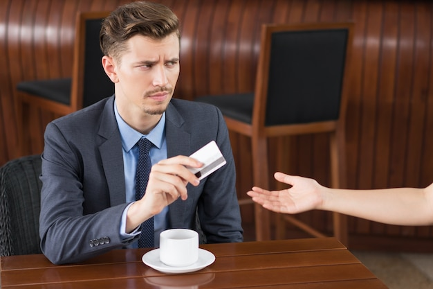 Suspicious Businessman Giving Card to Cafe Waiter Free Photo