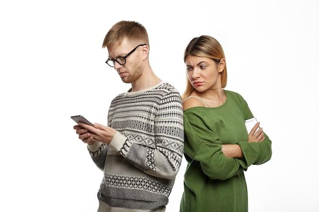Sospettosa diffidente giovane donna bionda in top verde in piedi accanto al suo fidanzato barbuto, guardandosi alle spalle, spiandolo mentre sta scrivendo un messaggio usando il cellulare Foto Gratuite