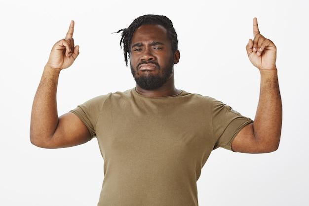 Подозрительный парень в коричневой футболке позирует на фоне белой стены Бесплатные Фотографии