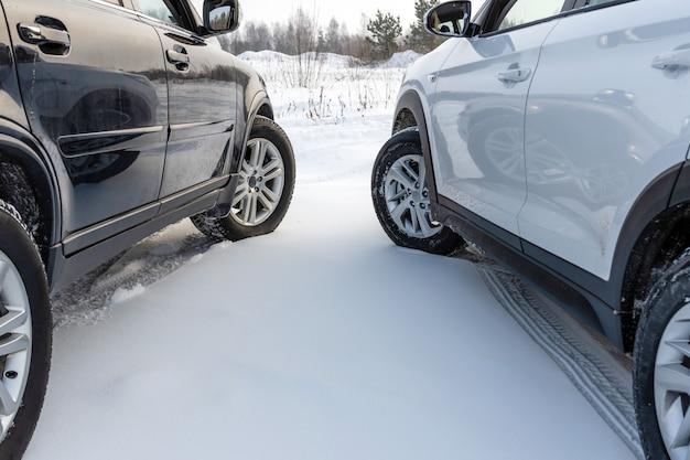 雪原に駐車している白と黒のsuv車。 Premium写真