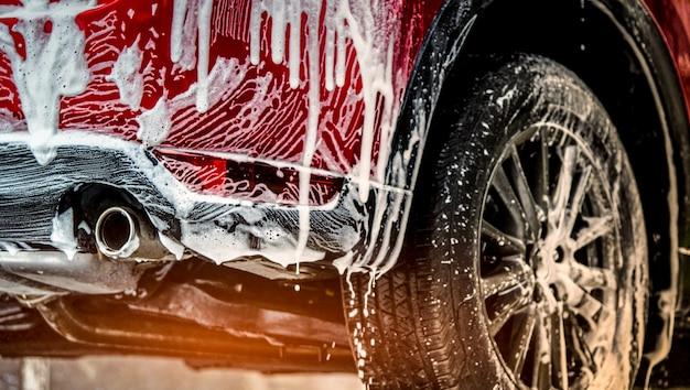スポーツとモダンなデザインの赤い小型suv車。石鹸で洗う。白く覆われた車 Premium写真