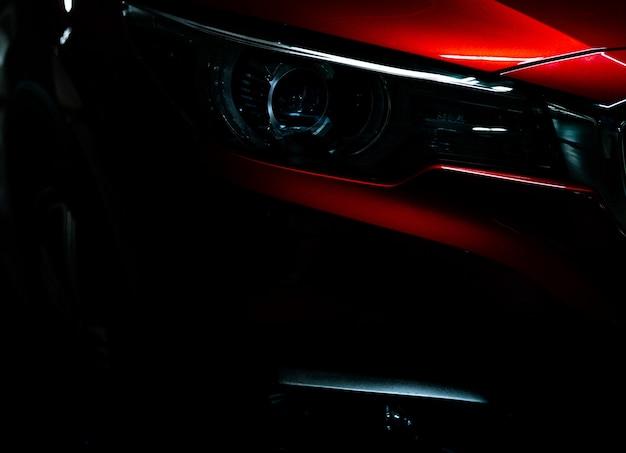 光沢のある赤い高級suvコンパクトカーのクローズアップヘッドライト Premium写真