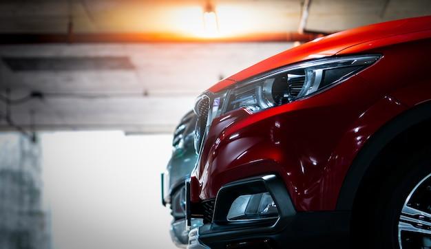 ショッピングモールの屋内駐車場に駐車されている赤い光沢のあるsuvスポーツカーにセレクティブフォーカス。エレガントで豪華なデザインのヘッドランプライト。自動車産業とハイブリッドカーのコンセプト。地下駐車場。 Premium写真